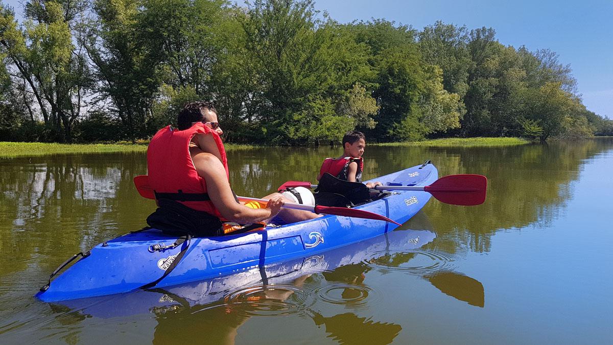 Hombre y niño montando en canoa por el río