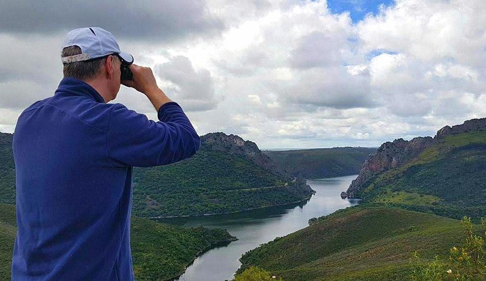 Hombre mirando con prismáticos el Cerro Gimio