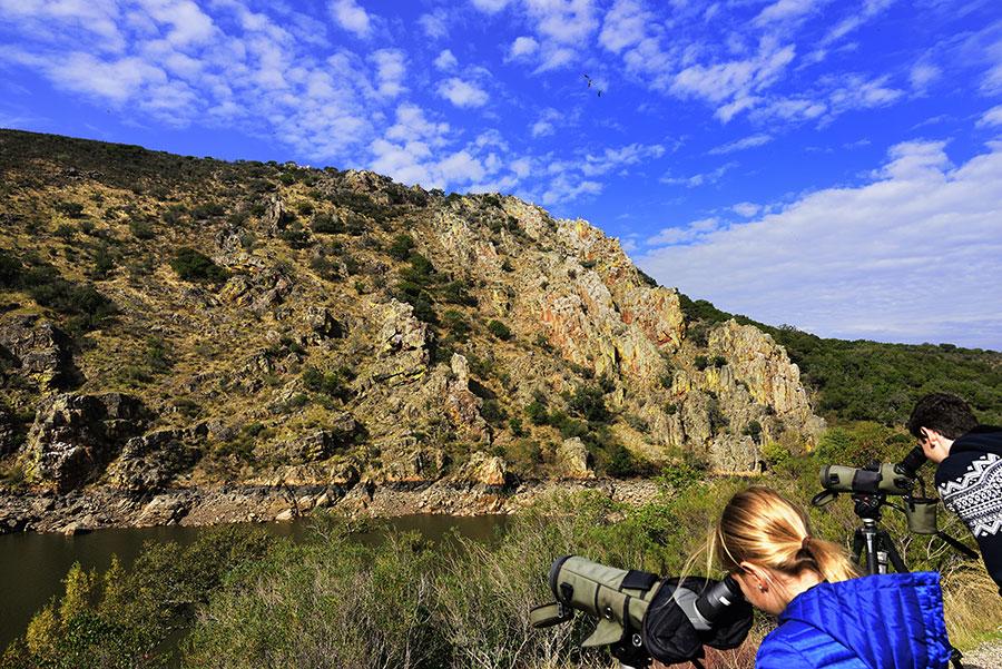 Turistas observando el paisaje del río con telescopio